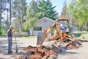 photo of backhoe doing excavating for new accessible sidewalk, siskiyou smokejumper museum, cave junction, oregon