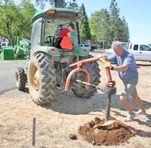 Photo of farm tractor drilling a hole for exhibit stands at siskiyou smokejumper museum, cave junction, oregon