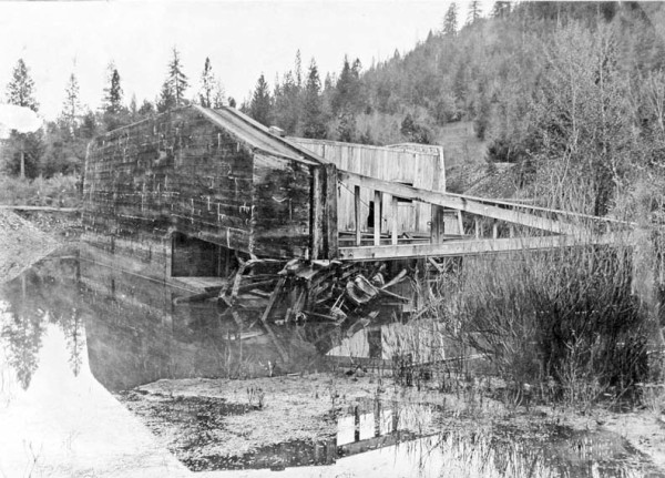 Photo showing the Josephine gold dredge on its side in a pond near Takilma, southwestern Oregon