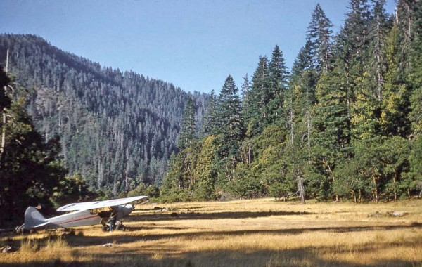 Photo of plane parked at Collier Bar airstrip in 1958. Illinois River in southwest Oregon