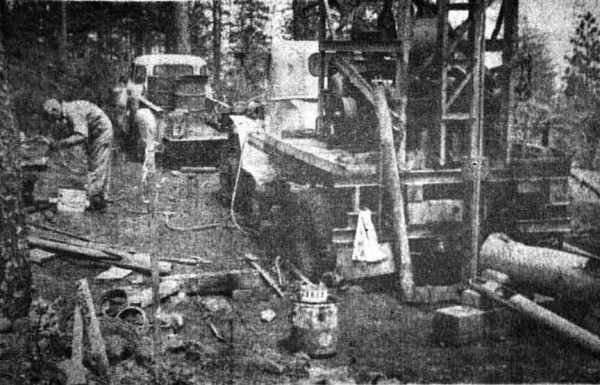 Newspaper photo of a drill rig taking core samples during nickel exploration on Woodcock Mountain, Cave Junction, Oregon