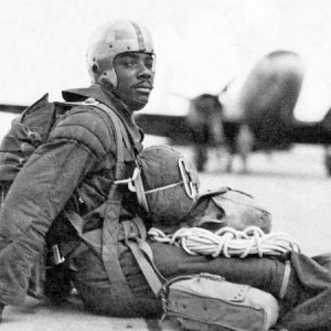 Historic photo of 555th Parachute Infantry Battalion soldier sitting on tarmac with aircraft in background