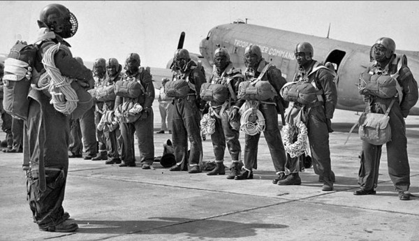 Photo showing 555th Parachute Infantry Battalion standing in full gear with an airplane in the background.
