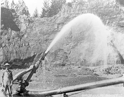 Photo of Chinese man operating hydraulic mining equipment near Waldo Oregon. Siskiyou Mountain History, Cave Junction, Oregon
