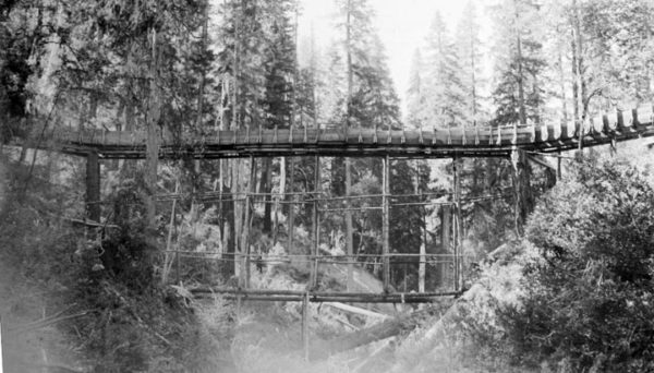 Historic photo showing a water flume made of wood crossing a gully.